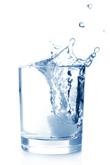 Ice in glass of water with splash on white background .
