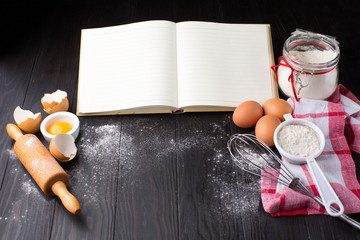 Recipe Cooking book, fresh eggs and Wooden kitchen Utensils on dark rustic wooden background. Selective focus with copy space.