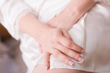 Mani rilassate di donna in vestaglia seduta appoggiate sulla coscia dopo la manicure