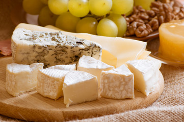 Various types of cheese served with grapes, walnuts and honey
