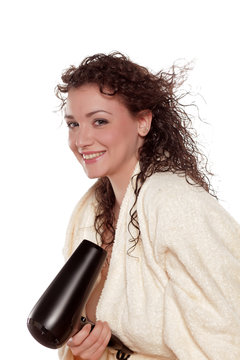 smiling young woman dries her hair with a blow dryer