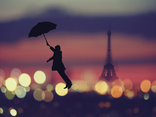silhouette of a man holding umbrella flying  over night Paris , France with eiffel tower on a background.