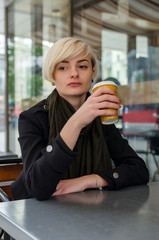 Young girl with a plastic cup of coffee