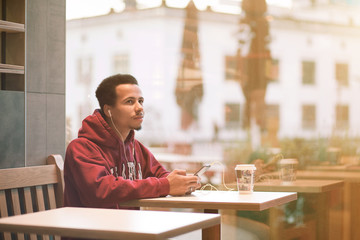 young african man sitting at a cafe and listening music from his mobile phone