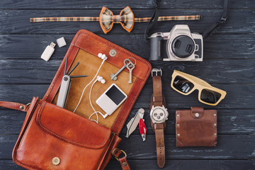 Outfit of traveler, student, teenager. Top view of essentials for modern young person. Different objects on black wooden background: leather bag, camera, player, sunglasses, watch, wallet, bow tie