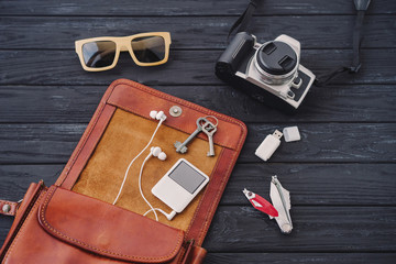Outfit of traveler, student, teenager. Top view of essentials for modern young person. Different objects on black wooden background: leather bag, camera, player, sunglasses, keys, usb flash, knife