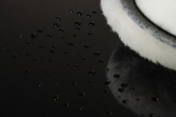 ausschnitt von polierpad auf schwarzem autodach mit wassertropfen und hochglanzlack