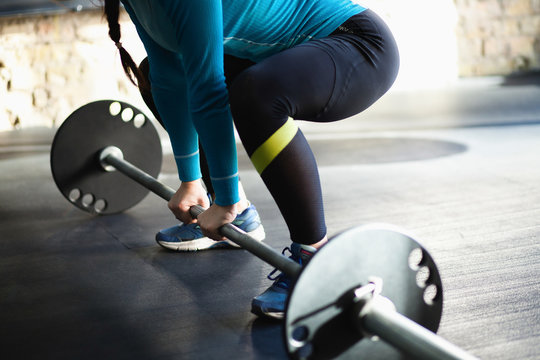 Muscular woman in a gym doing deadlift