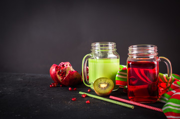 Smoothies of kiwi juice pomegranate juice in the jar with a handle on a dark background