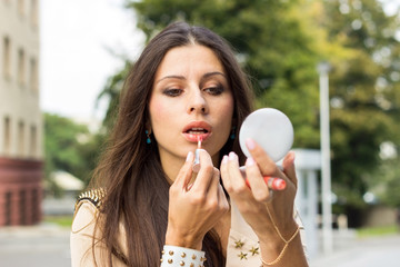 Young woman applying make up on the street