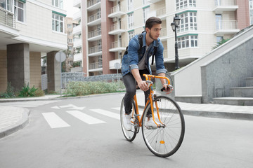 guy in denim jacket goes to school on bike. Cyclists the road in the city