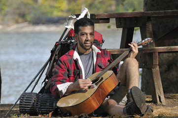 Backpacker Playing Guitar on Campsite