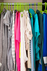 Women's clothes hanging on hangers in the wardrobe. Hangers in a