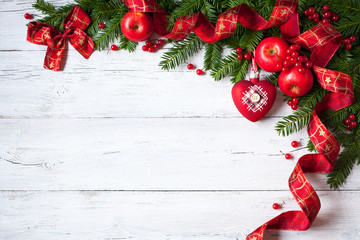 Christmas wooden background with branches of trees, apples, berries and red ribbon