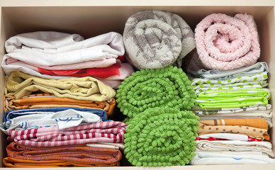 Bedding is in the closet on the shelf. Towels folded in a roll.