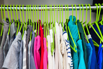 Women's clothes hanging on hangers in the wardrobe.