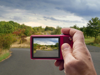 Autumn road with cloudy sky in camera viewfinder