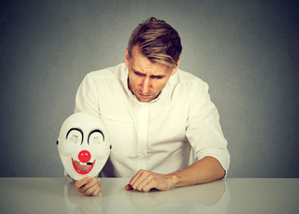 worried man with sad expression holding clown mask expressing cheerfulness