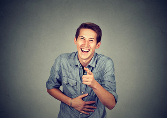 Portrait laughing young man pointing with finger