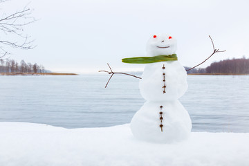 Portrait of very nice, smiling snowman with green scarf in winter on the lake background. Positive mood.