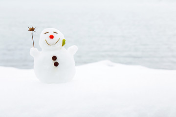 Portrait of very small, nice, smiling snowman in winter on the lake background. Positive mood.