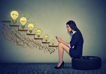 Woman sitting on wheel in front of growing up light bulbs using mobile phone