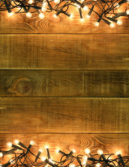 Christmas and New Year background with decorations glowing garland lights lamp on rustic wooden table board. Copyspace wit place for text or logo. Concept backdrop for announcements shop hallyday sale