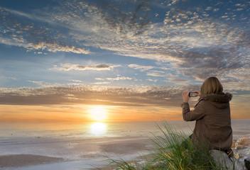 femme prenant le coucher de soleil
