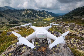 Flying drone quadcopter above the mountain hills