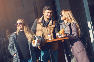 Group of cheerful young people talking, drinking coffee and eating croissant in cafe outdoor on sunny day. Concept togetherness, friendship, communication. Spending time with friends.