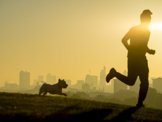 Defocus silhouettes of jogger and his dog run in front of the golden sunrise city skyline in London