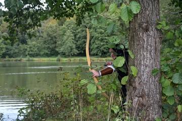 Mittelalterlicher Bogenschütze mit schwarzer Kapuze steht versteckt hinter Baum am See