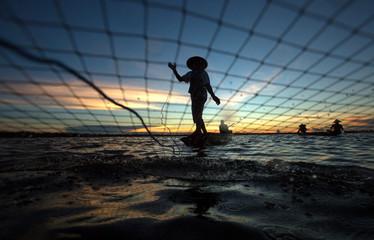 Silhouette fisherman are fishing net