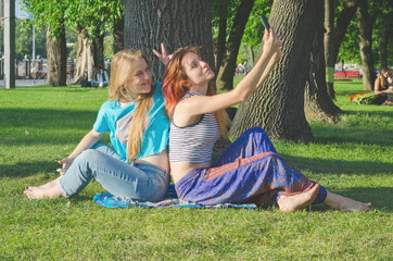 Girls in casual clothes in summer park watching videos and photos on a smartphone and pointing at screen. Girlfriends laughing and having fun outdoors. Concept of modern communication
