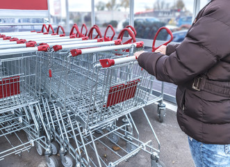 A woman takes a shopping trolley going shopping in a store
