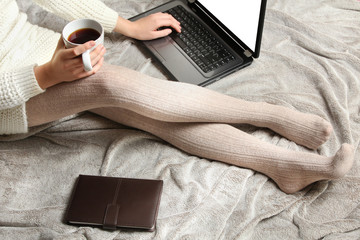 Girl with a laptop in her hands sitting on the bed. Top view