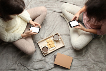 Girls with smartphones in their hands are sitting on the bed.