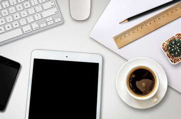 workplace with blank screen smartphone, tablet, coffee cup, paper and notebook on white wooden table
