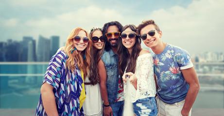 happy hippie friends with selfie stick over city