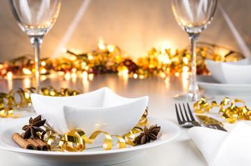 Weihnachtlich, festlich dekorierter Tisch mit Geschirr und Bokehhintergrund