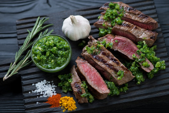 Sliced barbecued rump steak with chimichurri sauce, close-up