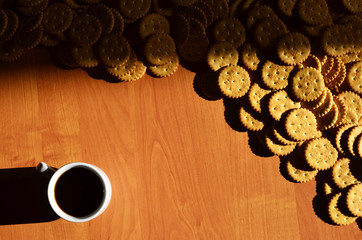 Background image of a small white cup of coffee and classic salty cracker on a brown wooden table