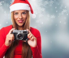 portrait of a beautiful young woman at Christmas taking a photo with her camera