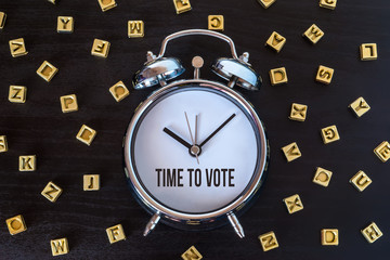 Time to vote - Alarm clock on wooden table with letters