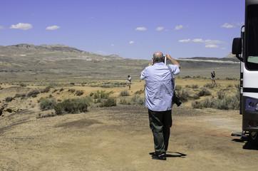Senior Citizen Videoing Family In Desert with RV