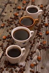 Four cups of coffee, hazelnuts and cocoa beans on wooden background
