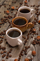 Three cups of coffee, hazelnuts and cocoa beans on wooden background