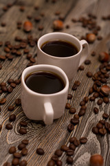 Two small white cups of coffee, hazelnuts and cocoa beans on wooden background