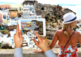 Tourist man taking picture with touch pad in Oia town on Santorini island. Travel concept.  Europe summer travel destination in Greece, Caldera, Aegean sea.;