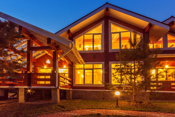 New Log Home with Large Porch at dusk